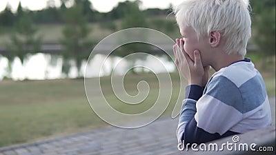 Un garçon blond riant joyeux sur une promenade banque de vidéos