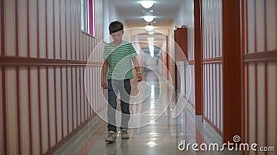 Un garçon se promène dans un long couloir d'un établissement d'enseignement banque de vidéos