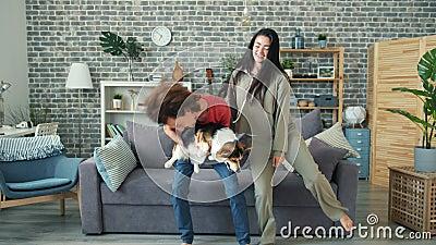 Un gars joyeux qui danse avec une petite amie tenant un chiot de corgi qui s'amuse à la maison banque de vidéos