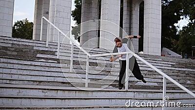 Un giovane biondo con pantaloni neri larghi e una bendatura rossa sui capelli gli fa un bel capovolgimento sopra le scale delle r stock footage