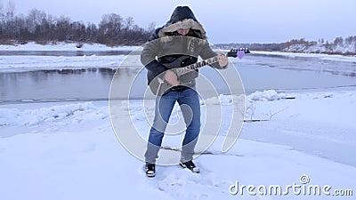 Un giovane nell'inverno per giocare la chitarra archivi video