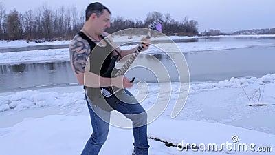 Un giovane nell'inverno per giocare la chitarra video d archivio