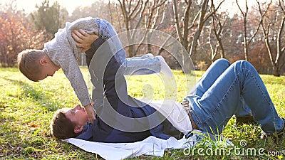 Un giovane padre gioca con un bambino, tenendolo tra le braccia I raggi del sole penetrano gli alberi La risata e la gioia archivi video