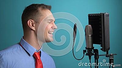 Un giovane uomo con una cravatta che canta in un microfono chiusura archivi video