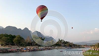 Un globo colorido grande vuela sobre el río en Laos almacen de metraje de vídeo