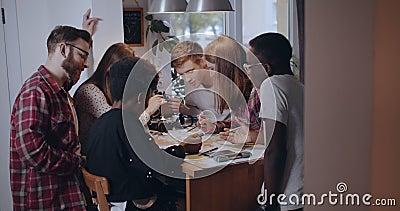 Un groupe de jeunes amis étudiants multiethniques heureux regardent la grande carte sur la planification de la table aventure voy banque de vidéos