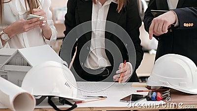 Un grupo de ingenieros trabaja en una oficina con un plan de la casa sostenga una tableta digital y discuta los planes con uno a  metrajes