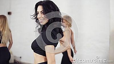 Un gruppo di ballerini femminili che imparano gli elementi della conduttura di bachata Torcendo corpo ed agitazione della testa M stock footage