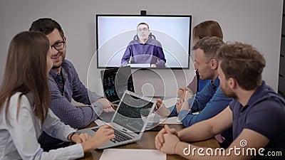 Un gruppo di specialisti finanziari guarda allo schermo con il capo azienda durante le videoconferenze in sala riunioni video d archivio