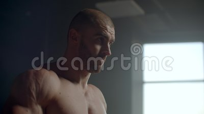 Un hombre atlético fuerte eleva los pesos entrenando los músculos trapezoides almacen de metraje de vídeo