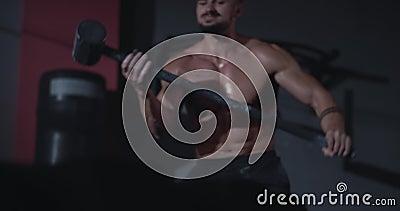 Un hombre atlético fuerte y concentrado eleva el gran humilde y golpea sobre un gran neumático en clase cross fitness metrajes