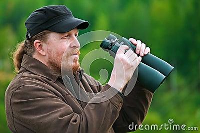 Un hombre barbudo con los prismáticos.