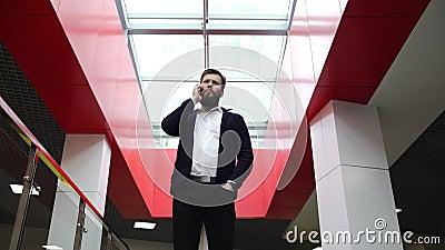 Un hombre barbudo de Brunette está hablando por teléfono de pie dentro del moderno edificio de oficinas, centro de negocios Joven almacen de metraje de vídeo