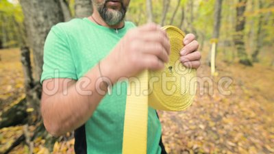 Un hombre barbudo de edad recoge una línea negra después de una lección en el bosque de otoño en equilibrio almacen de video