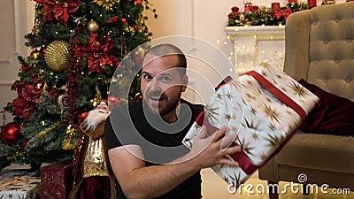 Un hombre bastante barbudo que se sienta cerca de un árbol de Navidad con un regalo almacen de metraje de vídeo
