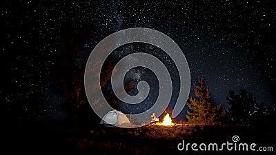 Un hombre cerca del fuego en la noche almacen de metraje de vídeo