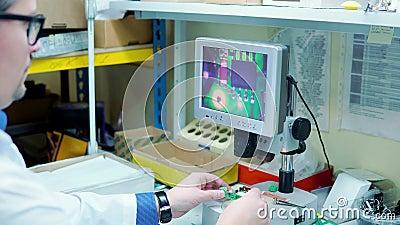 Un hombre con bata blanca y gafas revisa la placa eléctrica en busca de defectos a través de un dispositivo de aumento con una pa metrajes