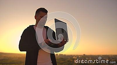 Un hombre con un ordenador portátil al atardecer se para en el techo del edificio y escribe un código en el teclado Hacker con po metrajes
