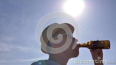 Un hombre con sombrero y gafas sacian la sed, se pone de pie bajo el sol brillante almacen de video