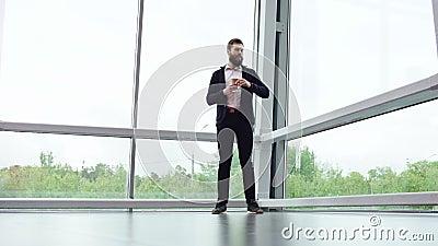 Un hombre de negocios de Brunette vestido con ropa informal está tomando café y esperando a alguien cerca de grandes ventanas pan almacen de metraje de vídeo