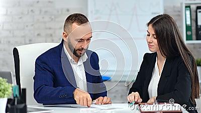 Un hombre de negocios y una mujer de negocios sonriente firmando un acuerdo contractual, haciendo que el trato se tambalee almacen de metraje de vídeo