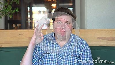 Un hombre hermoso, gordo con demostraciones grandes del cuerpo aprueba firma adentro el café o el restaurante almacen de video