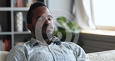 Un hombre joven africano tranquilo medita en el sofá con los ojos cerrados metrajes