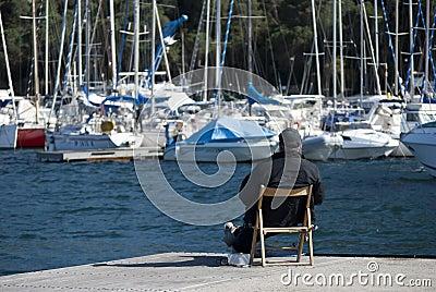 Un hombre que mira los barcos Fotografía editorial