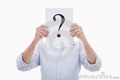 Un hombre que oculta su cara detrás de un signo de interrogación