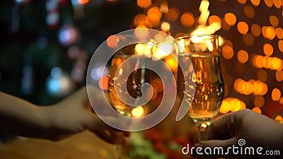 Un hombre y una mujer aumentan los vidrios de champán chispeante sobre una tabla festiva almacen de video