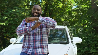 Un homme africain très excité tenant des clés de voiture pendues en voiture, achat de transport banque de vidéos