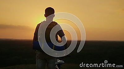Un homme avec un sac à dos et une bicyclette Il tient et regarde l'horizon où le soleil place Recyclage et aventure clips vidéos