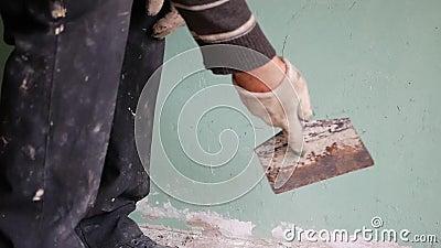 Un homme avec une spatule. un homme aux cheveux gris fait des réparations à domicile. alignement des murs. développeur de gros. banque de vidéos