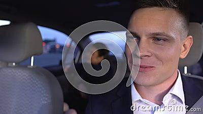 Un homme beau en costume attend une femme en auto et sourit, se sentant affection banque de vidéos