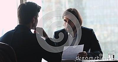 Un homme d'affaires couronné de succès discutant des détails du contrat avec son partenaire banque de vidéos