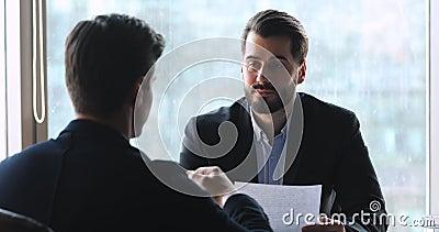 Un homme d'affaires intelligent discutant des détails du contrat avec son partenaire de bureau banque de vidéos