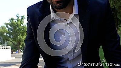 Un homme d'affaires passionnant avec une barbe s'assoit dans une chemise et une veste dans le parc et travaille sur un ordinateur  banque de vidéos