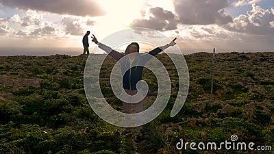 Un homme dans le hoodie bleu soulève ses bras contre le contexte de la nature, des roches, de la mer, de la mousse verte et des s banque de vidéos