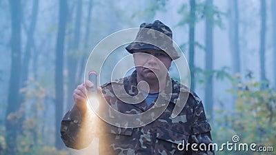 Un homme en camouflage se promène dans la forêt avec une lampe de poche dans la main Météo pluvieuse humide tôt le matin banque de vidéos
