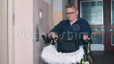 Un homme en fauteuil roulant attend un ascenseur dans un immeuble résidentiel banque de vidéos