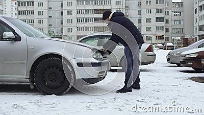 Un homme essaie et ne peut pas ouvrir le capot de sa voiture en hiver dans le parking de la cour Bonnet gelé à cause du froid banque de vidéos