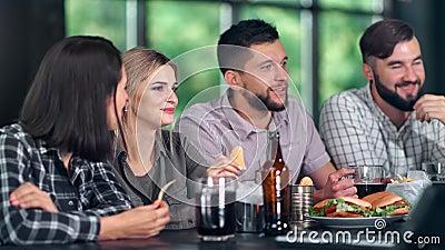 Un homme et une fille attirants se relaxant au pub en regardant la télévision parler du championnat de football sportif clips vidéos