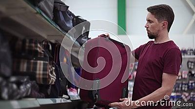 Un homme examine une valise dans une zone de commerce banque de vidéos