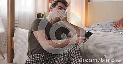 Un homme hurlant et SMS sur son téléphone portable à la maison banque de vidéos