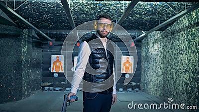 Un homme insère la cartouche chargée dans un pistolet tout en se tenant dans un champ de tir banque de vidéos
