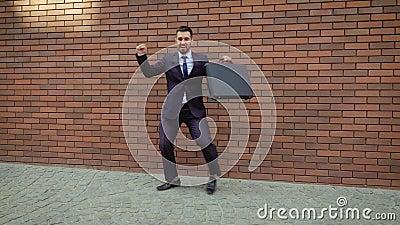 Un homme passionnant avec une barbe et une mallette dansant dans la rue de la ville Sur fond de mur de briques modernes banque de vidéos