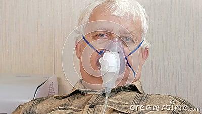 Un homme plus âgé tenant un masque d'un inhalateur à la maison Traite l'inflammation des voies aériennes par l'intermédiaire du n banque de vidéos
