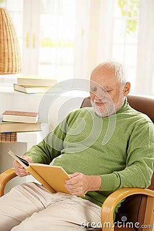 Un homme plus âgé détendant à la maison, livre de relevé