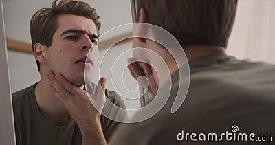 Un homme qui vérifie sa coiffure et son visage dans un miroir banque de vidéos