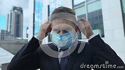 Un homme sérieux en costume avec un masque de protection, épidémie saisonnière de grippe dans le pays banque de vidéos